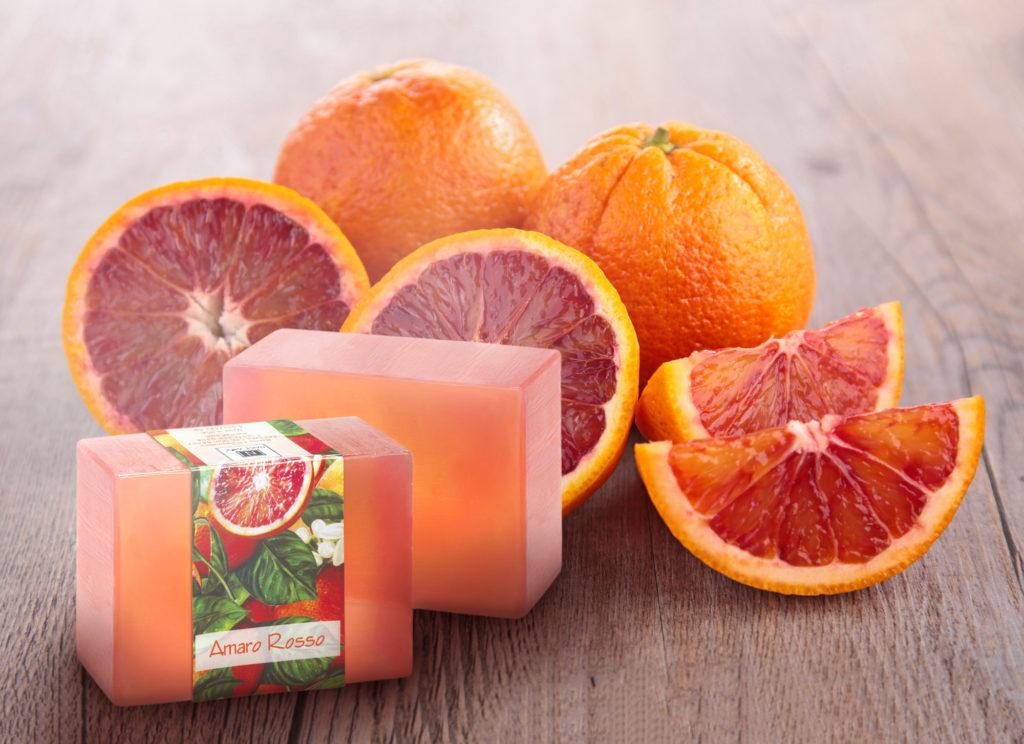 2 Bars of Nabila K's Amaro Rosso Full Bloom Glycerin Soap next to Sliced Blood Oranges