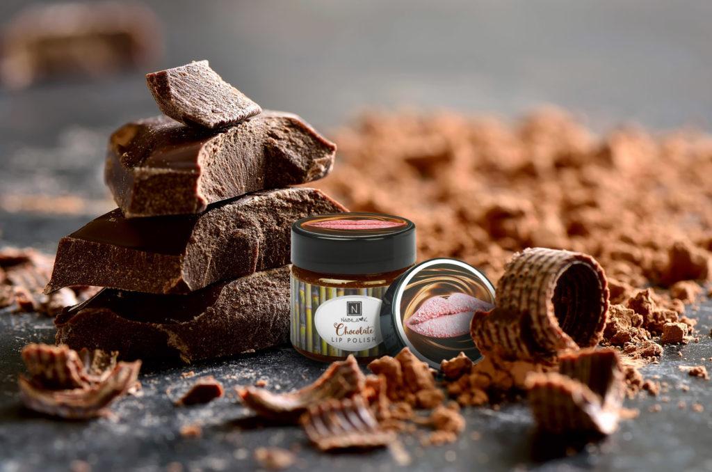 1 Jar of Nabila K's Chocolate Lip Polish Next to Chocolate Shavings and Chocolate Pieces