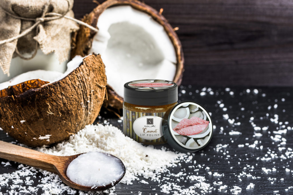 1 Jar of Nabila K's Coconut Lip Polish Next to a Coconut split in half and coconut shavings