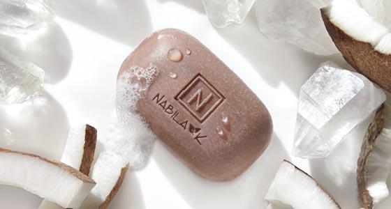 1 Bar of Nabila K's Crystal Etch Soap Next to Sliced Coconuts