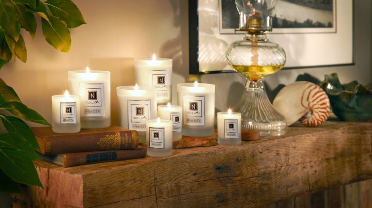 Collection of candles standing on the old timber in a cosy home environment.